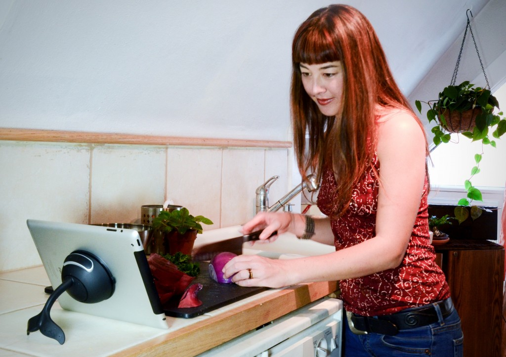 Woman prepares food in the kitchen while referring to her iPad which is being held upright by the Whale Kit iPad stand.